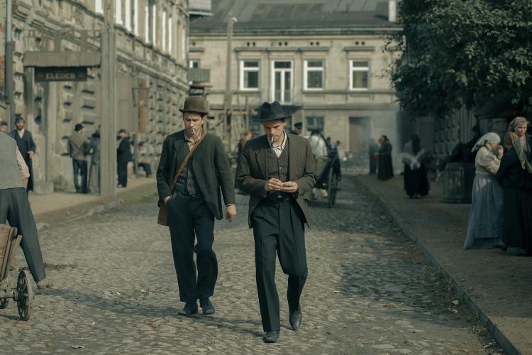 Dwóch mężczyzn w strojach z początku 19 wieku z papierosami w ustach, idących środkiem wybrukowanej ulicy, w tle kamienice i wóz