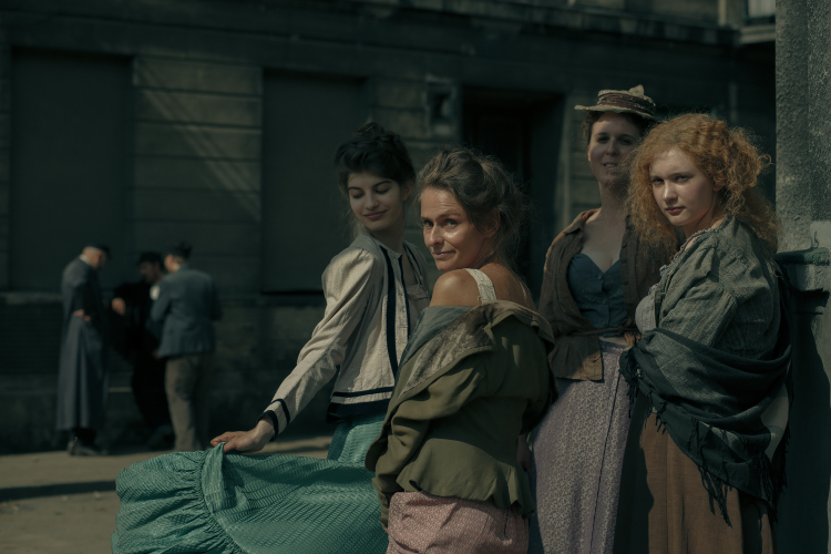 Cztery kobiety w sukniach z początku 19 wieku stojące i patrzące poza kadr, w tle kamienica i trzech mężczyzn