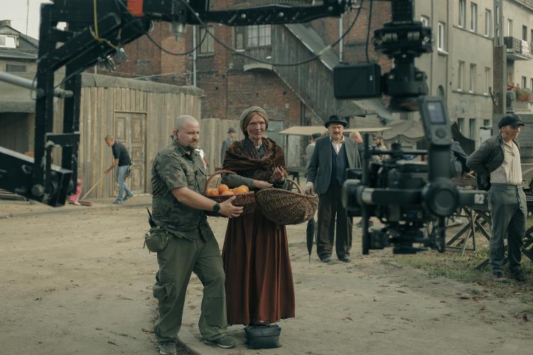 Rudowłosa starsza kobieta w brązowej sukni z koszem wiklinowym w ręku, obok mężczyzna z koszem pomarańczy otoczeni urządzeniami filmowymi