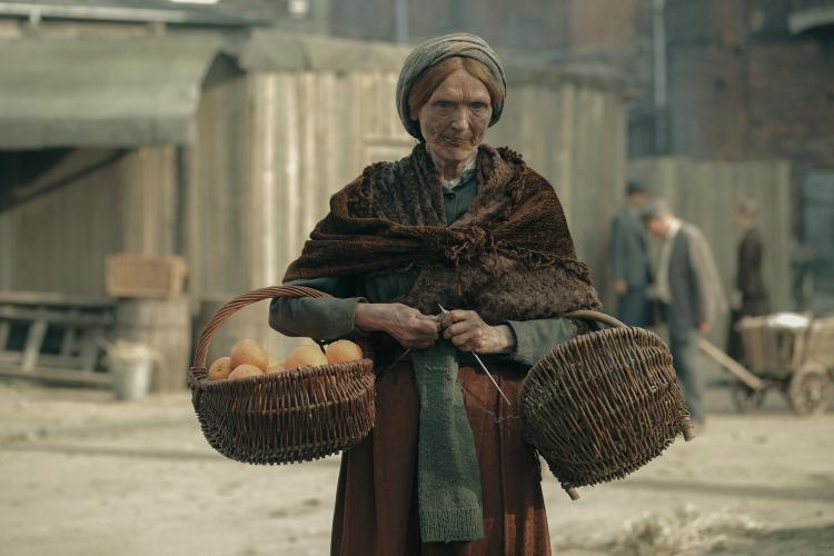 Rudowłosa starsza kobieta w brązowej sukni z koszami wiklinowym w rękach, jeden z pomarańczami