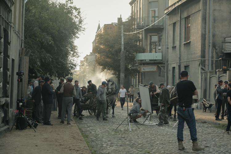 Wybrukowana kamieniami ulica pośród kamienic, aktorzy i filmowcy przygotowujący się do zdjęć, na środku wóz z koniem